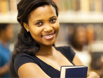 Female student close up, holding a book