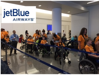 JetBlue logo and students of the Henry Viscardi School on line at airport terminal.