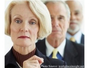 Aging Workers, a woman and two men behind her. Photo Source: http://workplaceinsight.net/