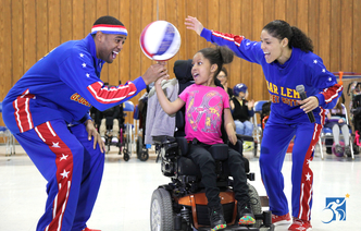 Man and woman Globetrotter spin basketball on student's finger.