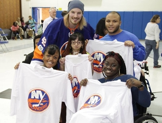 Mayfield poses with students holding NY Islander shirts.