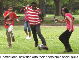 A group of youths playing soccer. Recreational activities with their peers build social skill.