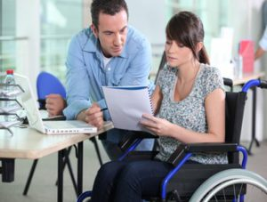 Young man leaning next to a young woman in a wheelchair reviewing a document.