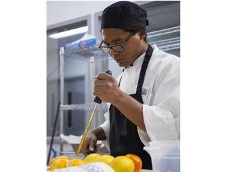 A young man zesting lemons