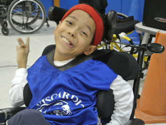 HVS student, Martin, smiling in a basketball jersey