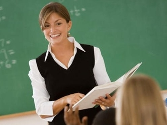 Female teacher in front of classroom.