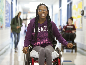 Young woman smiling in a wheelchair within a school setting