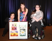 Luncheon performer, Kara Lindsay, is presented with framed artwork by two students.