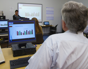 A man sits at a computer during a computer training course.