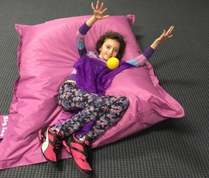 A young girl laying on a pillow throwing a ball.