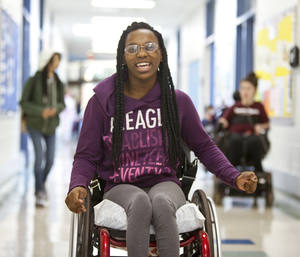 A young woman in a wheelchair in a school hallway.