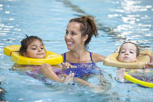 Female pool instructor with two students in an indoor pool.