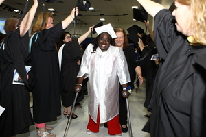 A young woman uses crutches to walk through the exit procession at her senior graduation.