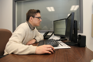 A young man sitting at a computer