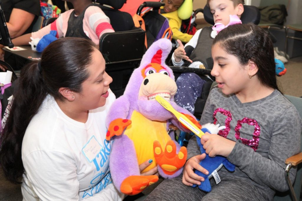 "[L-R] Registered Dental Hygienist Yocelyn Arevalo educates Henry Viscardi School student, Jana, during Project Accessible Oral Health's inaugural ""Take a Dental Health Day - Screening and Education for the Disability Community"" event on Friday, October 26 at The Viscardi Center's Albertson, New York campus. More than 200 children, teens and adults with disabilities were educated about the importance of oral healthcare and its impact on overall health."