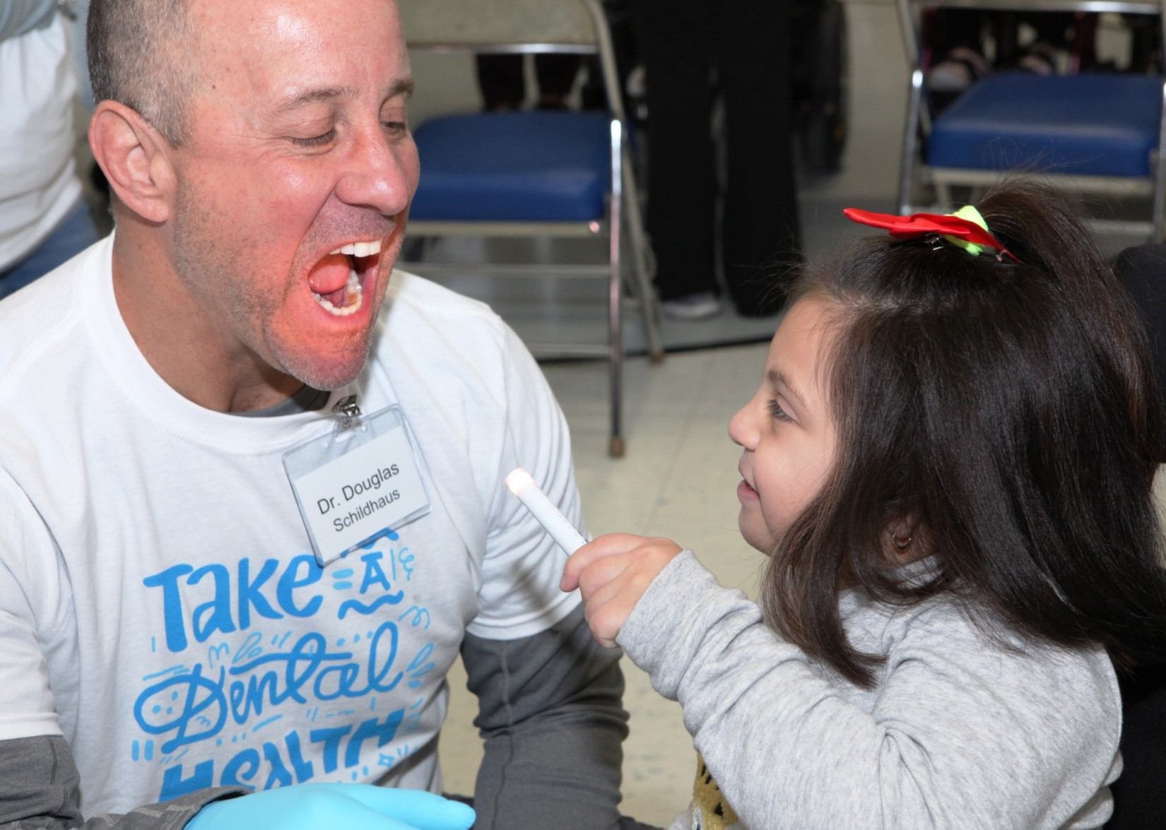 """Dr. Douglas Schildhaus undergoes a """"screening"""" from Henry Viscardi School student Victoria at Project Accessible Oral Health's """"Take a Dental Health Day: Screening and Education for the Disability Community"""" inaugural event, where more than 75 dentists, dental students, dental residents and volunteers were able to screen and educate more than 200 children, adolescents and adults with disabilities. The event took place on Friday, October 26 at The Viscardi Center's Albertson, New York campus."""