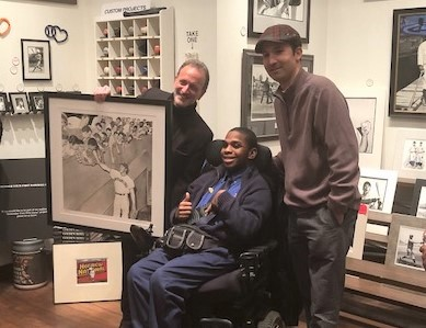 Jay Goldberg presenting artwork to a young man in a wheelchair.