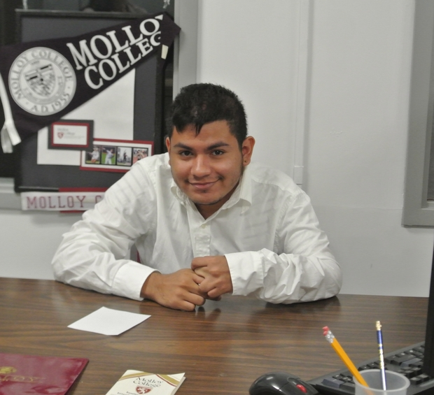 Miguel sitting at a desk.