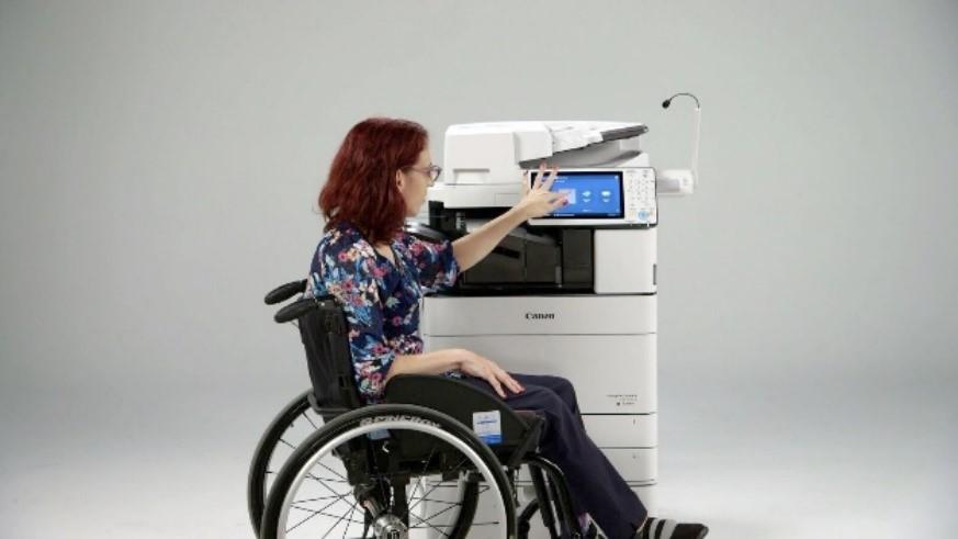 A woman in a wheelchair at a copy machine.
