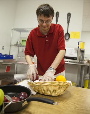 A young man prepping fruit in our culinary program.