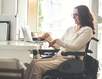 A young woman in a wheelchair typing on a laptop