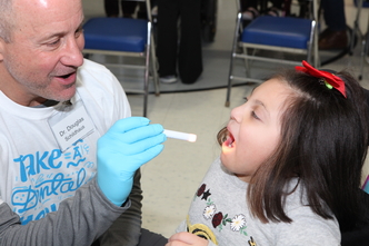 A dentist shines a flashlight into a young child's mouth during a dental screening