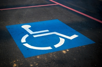 Universal handicap logo painted on the ground in a parking space.