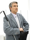 A man in a grey suit standing holding a white cane assistive device and black briefcase