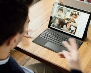 Young professional engaging in a video conference with four colleagues through his laptop.