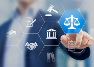 A man in business attire points to a touchscreen graphic featuring icons representing the legal system.